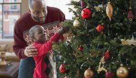 Father and son decorating Christmas tree