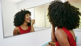 Mixed race woman applying makeup in mirror