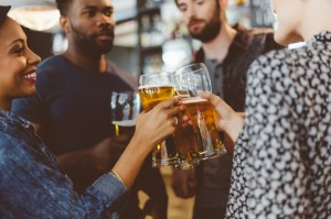 Friends toasting with beer in a pub