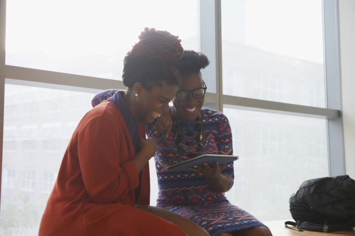 Smiling women using digital tablet