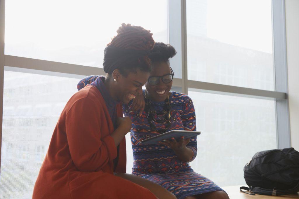 Smiling women using digital tablet