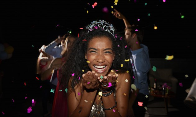 Young woman blowing confetti