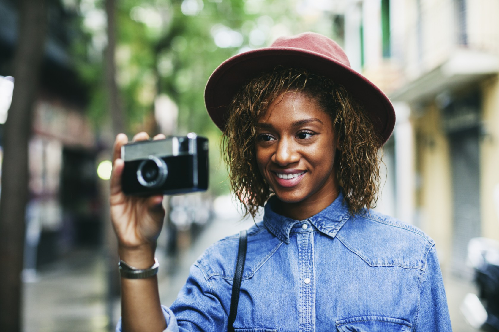 Portrait of smiling young woman wearing hat and denim shirt holding camera