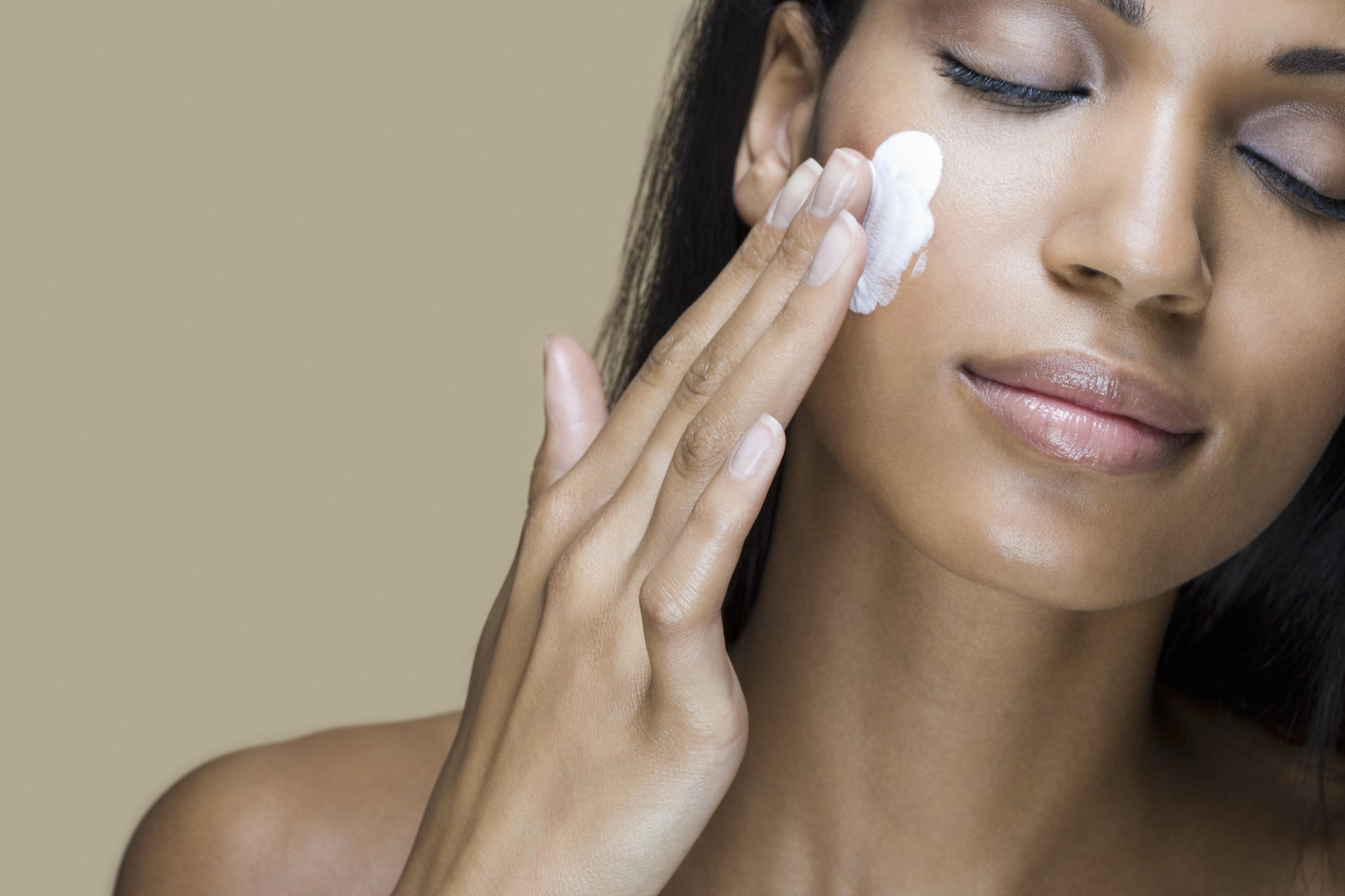 A woman rubbing moisturizer into her skin