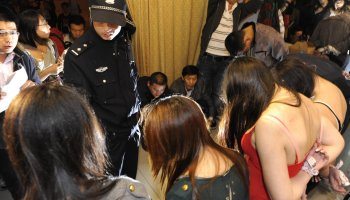 A Chinese police officer interrogates a