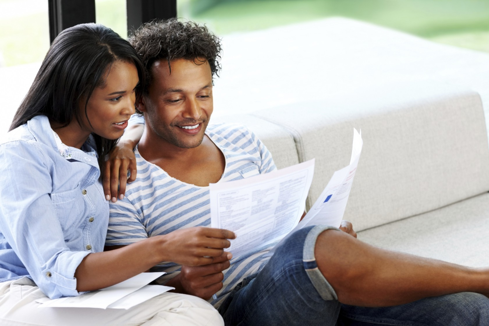 Young couple reading financial bill at home