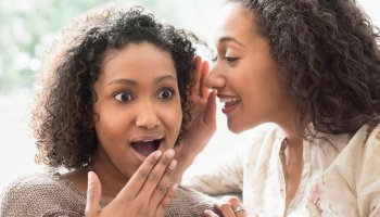 Surprised women whispering secrets