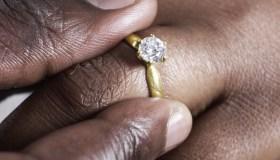 Man putting wedding ring on woman.