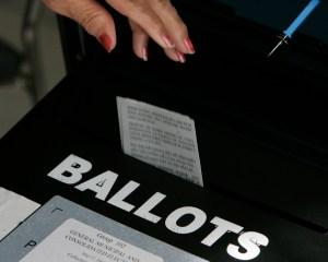 (Los Angeles)–Precinct workers drop ballots into the ballot box at the Pico–Aliso Social Hall polli