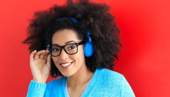 Young woman with blue headset and eyeglasses listening music