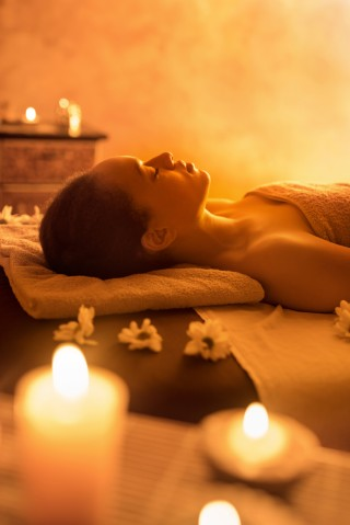African American woman lying at spa with eyes closed.