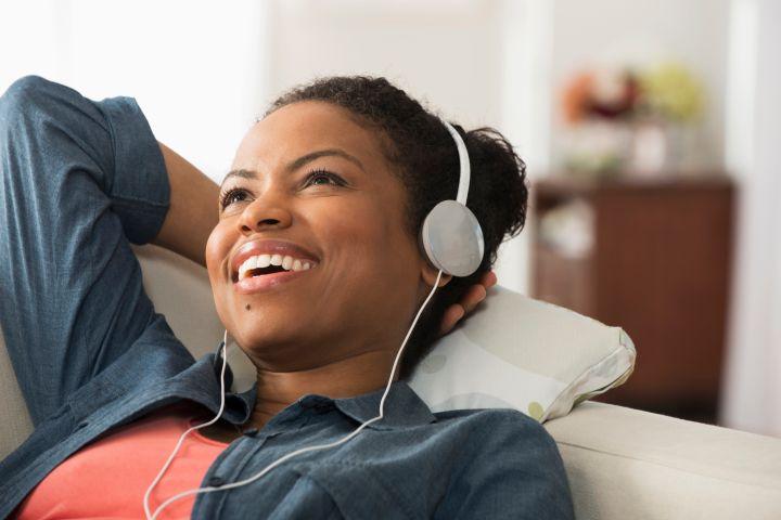Mixed race woman listening to headphones on sofa