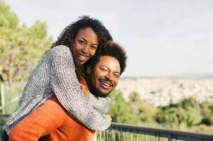 Spain, Barcelona, portrait of happy young man giving his girlfriend a piggyback ride