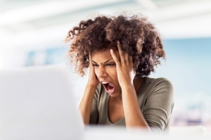 Angry African American woman using computer.
