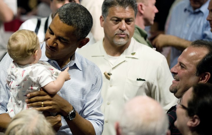 US President Barack Obama holds a baby a