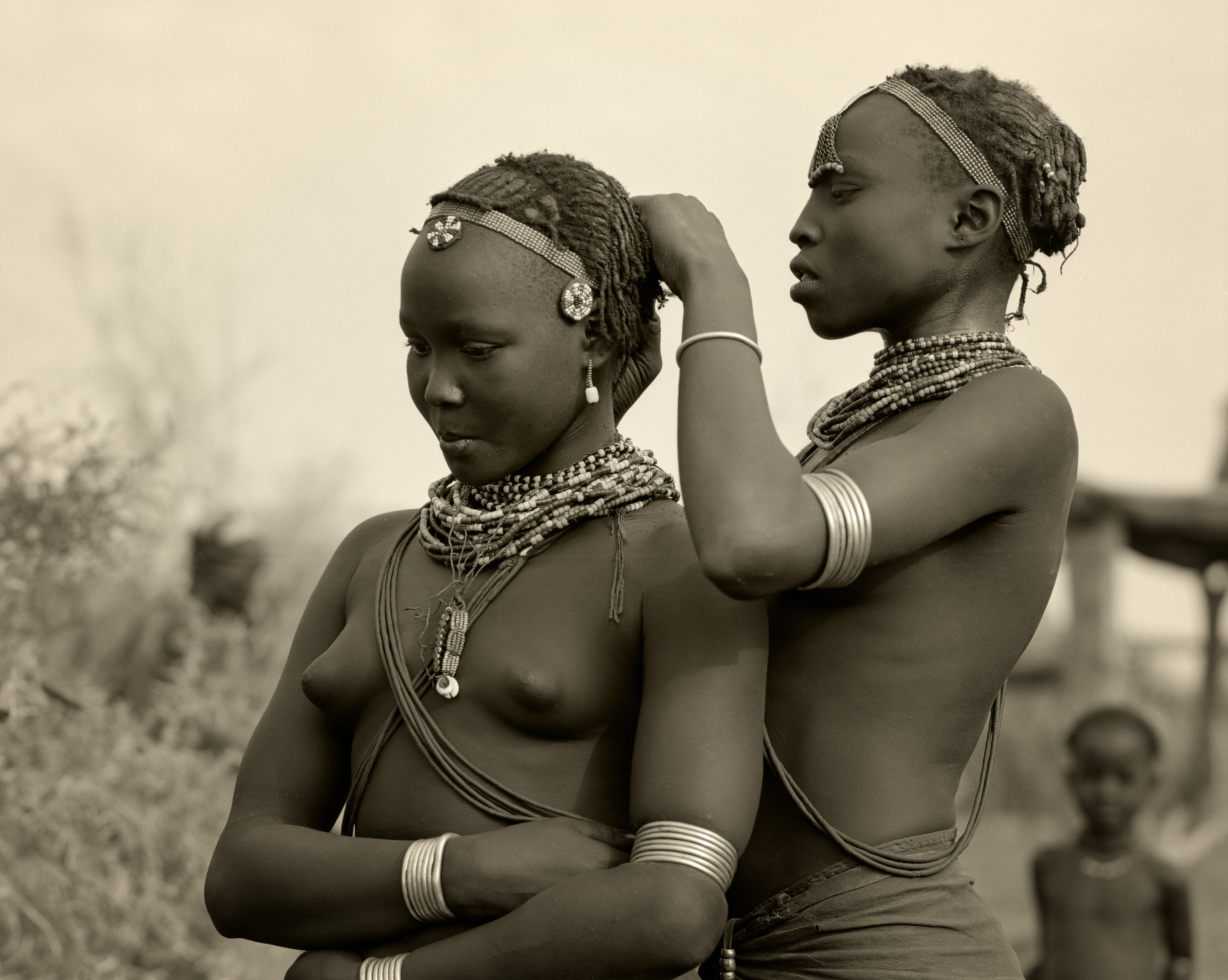 Ethiopia, Omo Delta. A Dassanech girl braids her sister's hair at her village in the Omo Delta