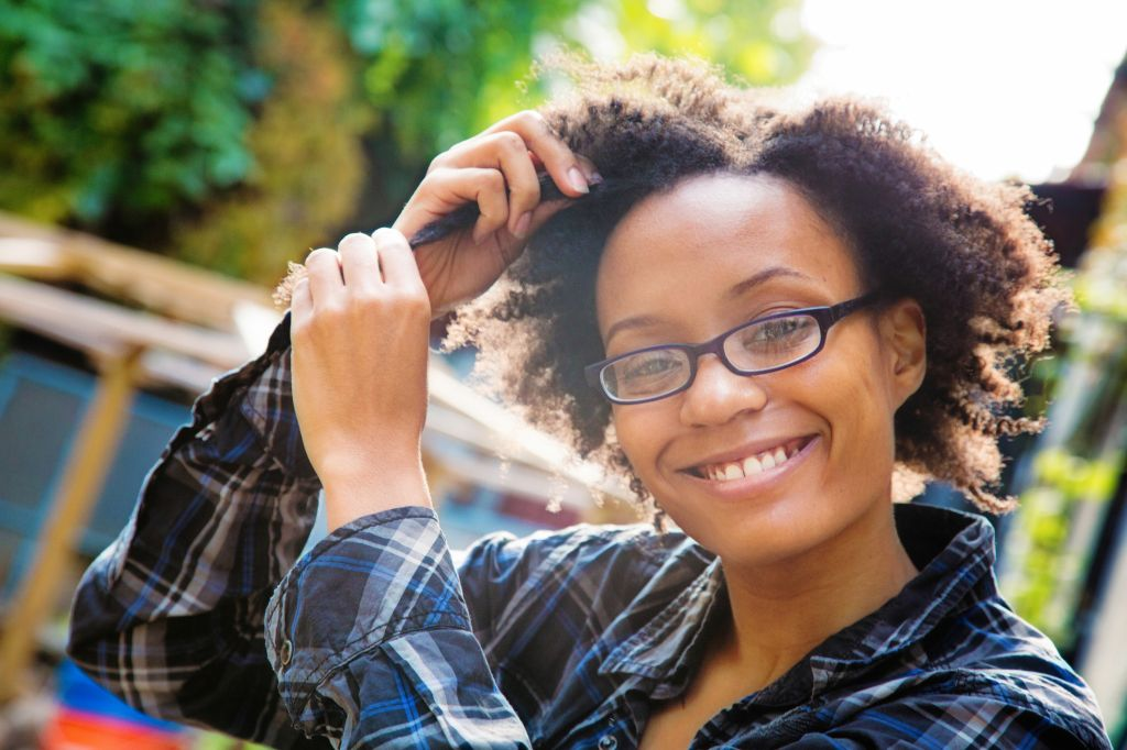 Confident happy young black woman arranging her hair outdoors