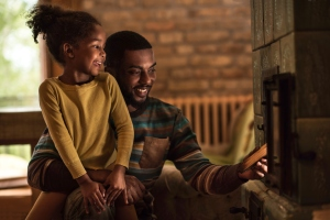 Happy father and daughter putting a wood into the fireplace.