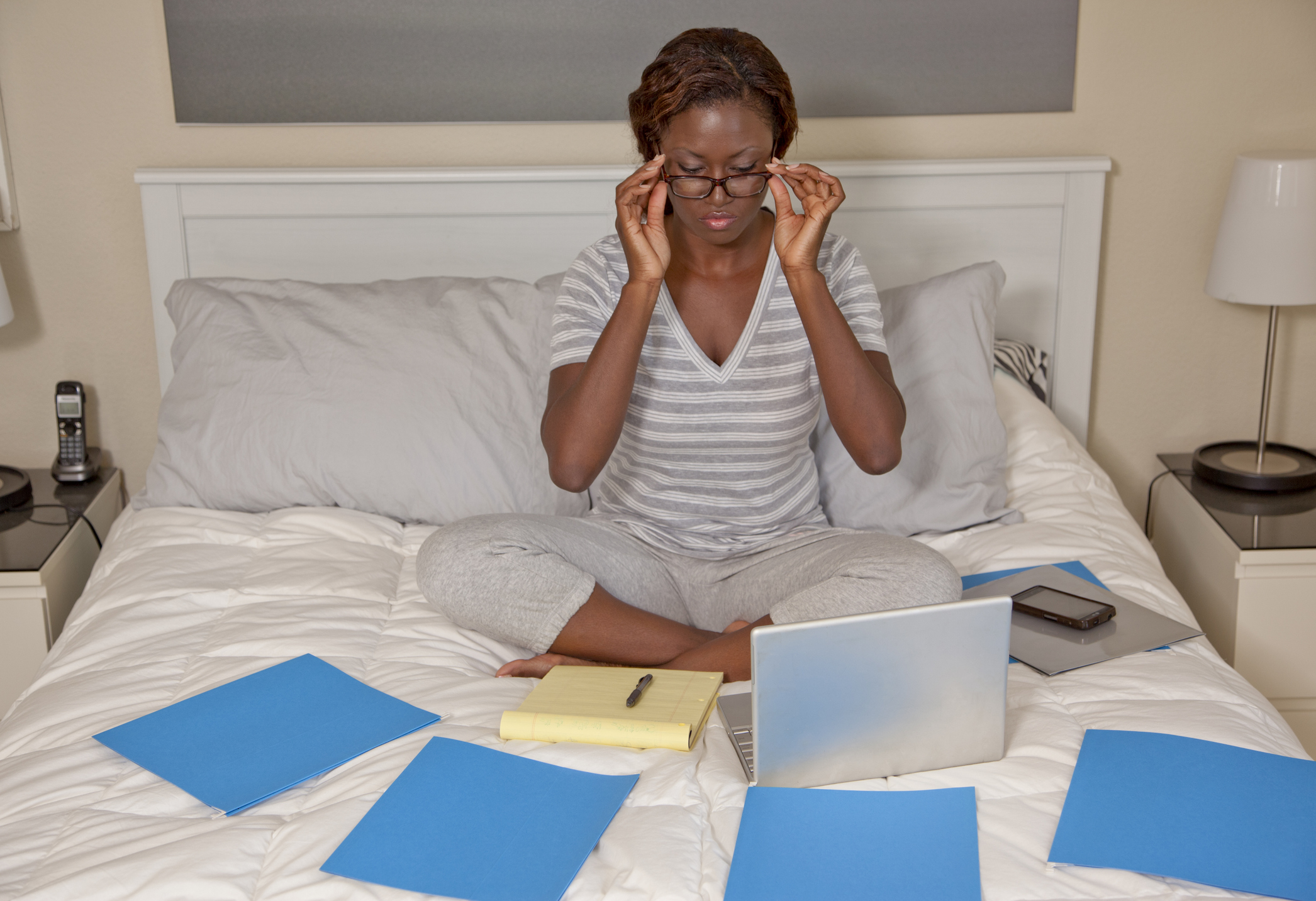 African American woman working from bed