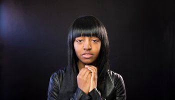 Beautiful young black woman on a black background