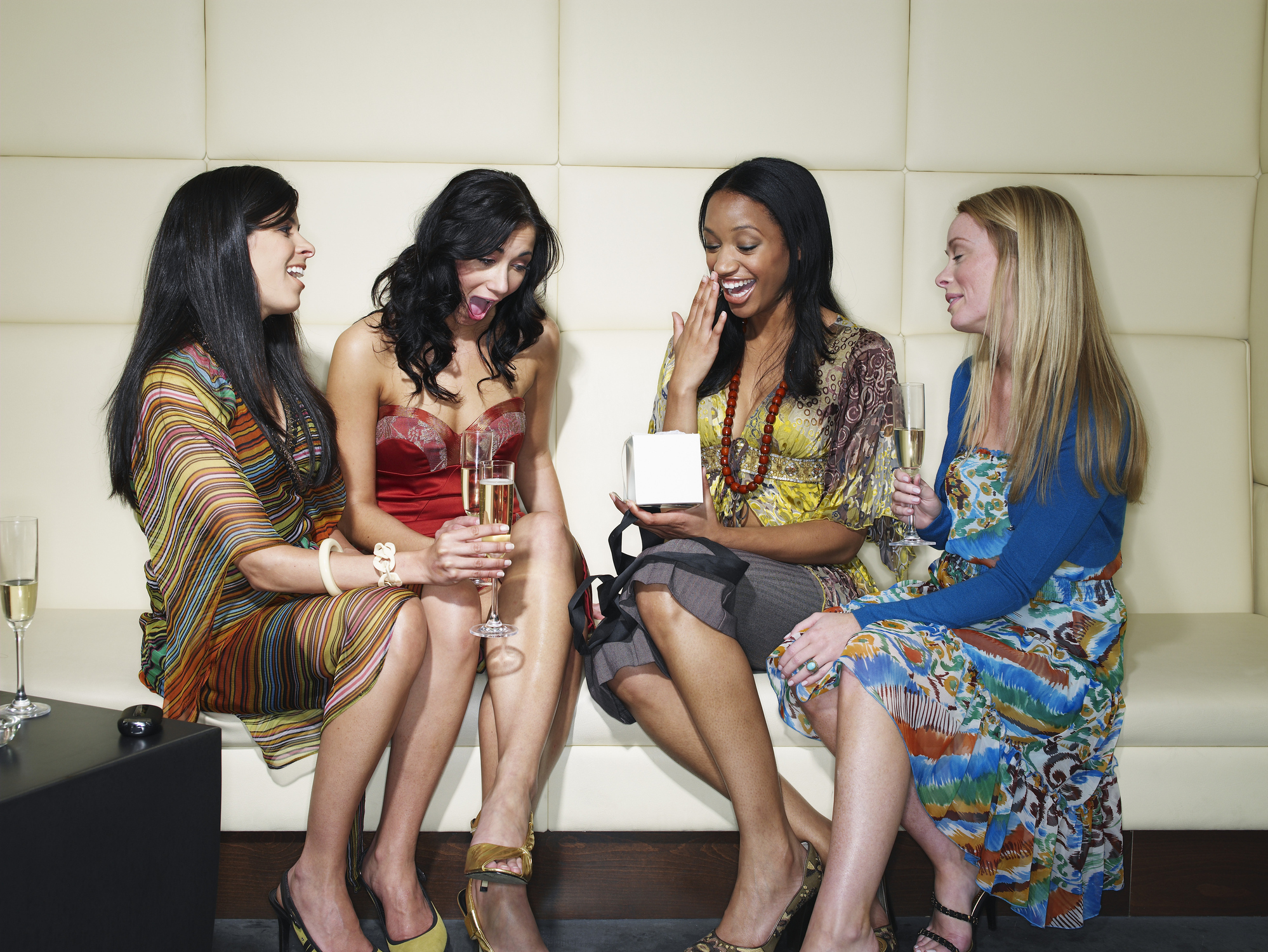Four young women drinking champagne in club, one woman opening gift