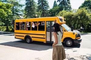 Group of elementary school kids in yellow school bus.