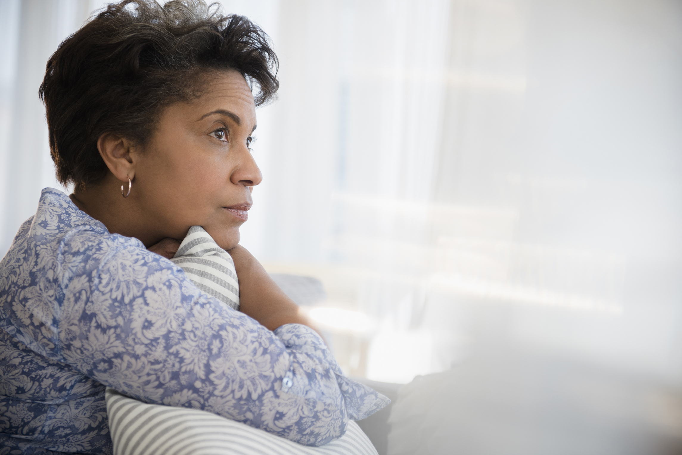Pensive older Black woman clutching pillow
