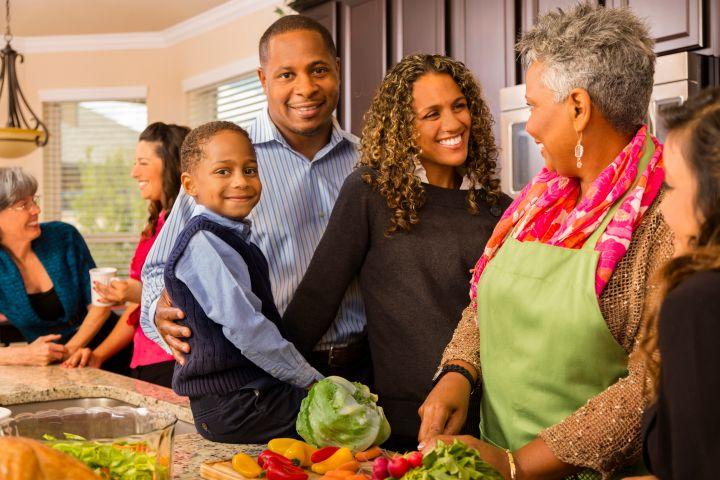 Relationships: Multi-generation family prepares dinner in kitchen.