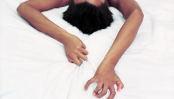 Woman Gripping Sheets During Lovemaking