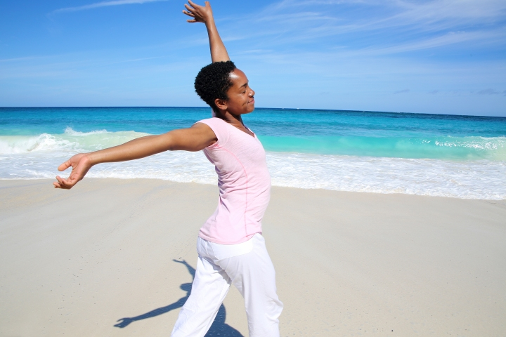 Cheerful Woman stretching at the Beach