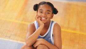 Female Basketball Player Sitting on Basketball