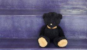 Black teddy bear sitting on the steps
