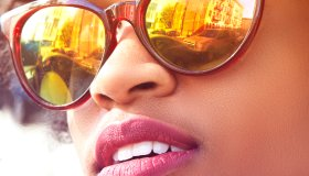 Close up portrait of young female fashion blogger with afro hair and mirrored sunglasses, New York, USA
