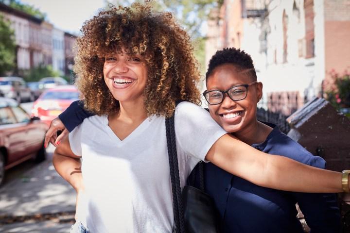 Portrait of Black women hugging on city sidewalk