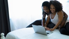 Lesbian couple sitting on bed, looking at laptop