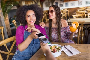 Cheerful frineds using smart phone for mobile payment