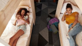 Young woman checking phone in bunk bed, roommate sleeping in the other bed