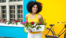 Smiling woman with bike carrying flowers in pot