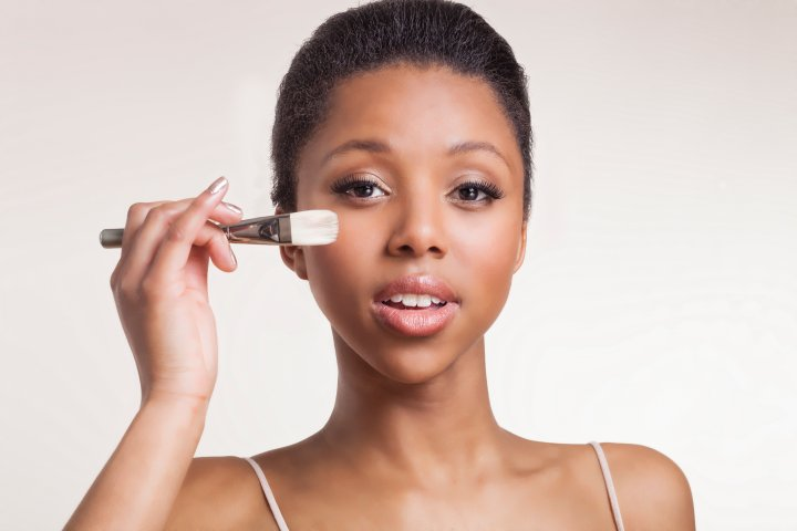 lady holding foundation brush near her cheek