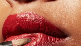 Tight beauty shot of womens face. Red lipstick and red makeup