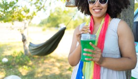 Smiling woman drinking green cocktail