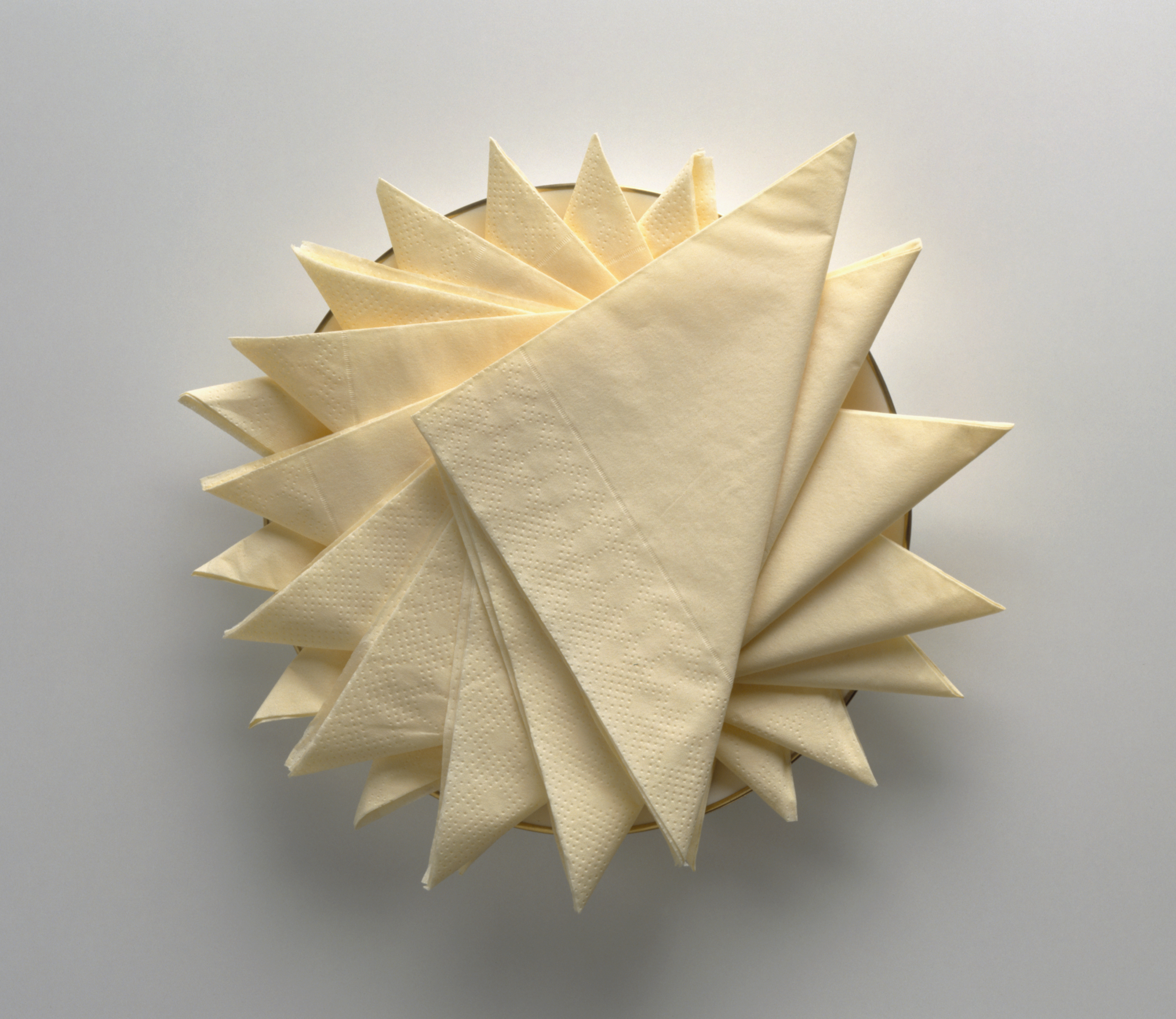 Stack of yellow paper napkins creatively arranged on plate