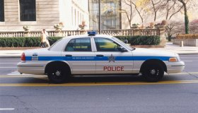 USA, Illinois, Chicago, police car driving along street, side view.