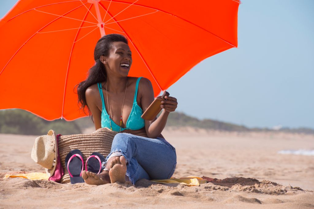 Relaxed woman holding sun protection cream on the sunny beach.