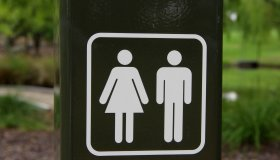 Sign post pointing to male and female public toilets in Weston Park, Yarralumla, Australian Capital Territory, Australia