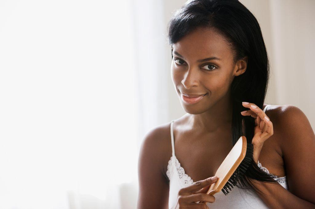 African woman brushing hair
