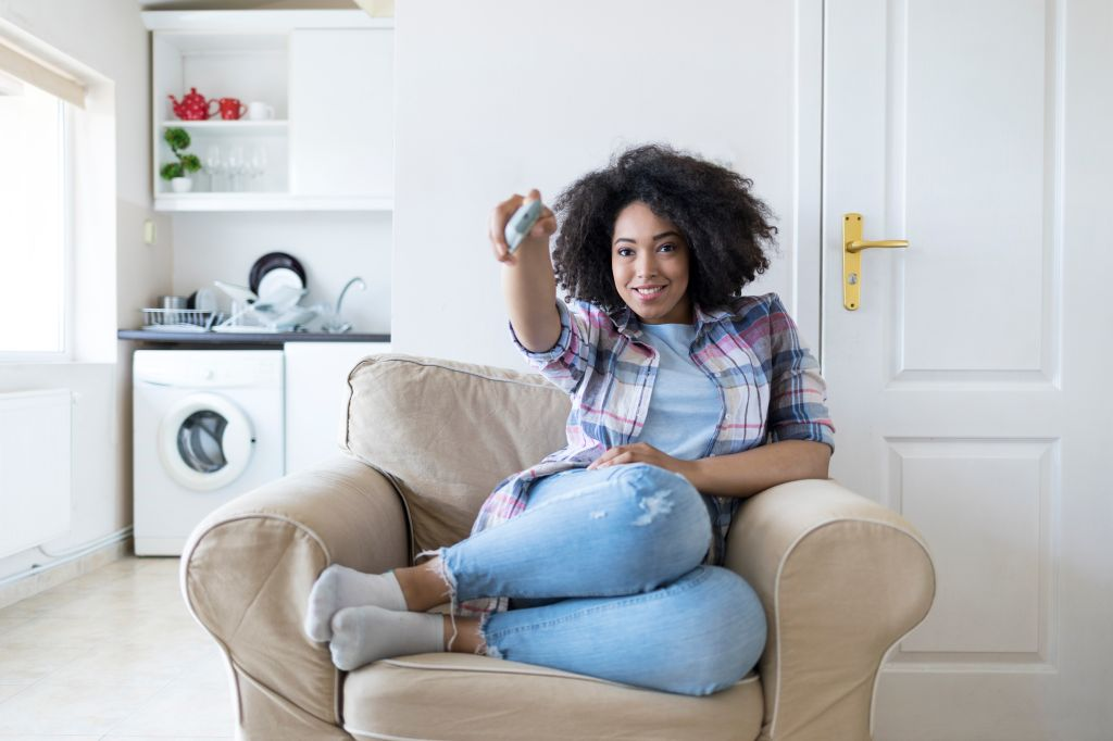 Woman resting at home and watching TV