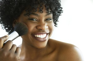 Young woman using make-up brush, smiling, portrait, close-up