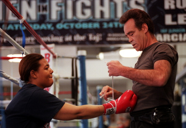 Boxer Freeda Foreman, daughter of former heaveyweight champion George Foreman, puts her gloves on with trainer Larry Goossen before working out at America Presents Gym in Denver.