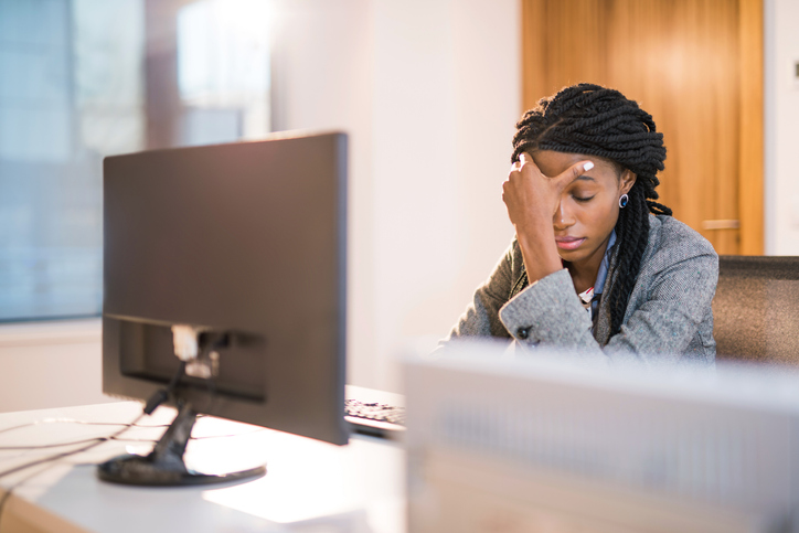 Depressed African woman at work.